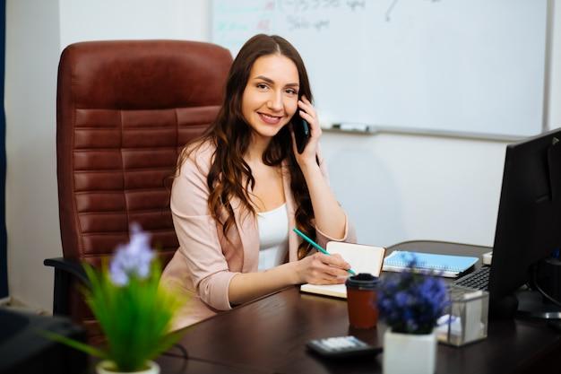 Молодая милая бизнес-леди с тетрадью в офисе