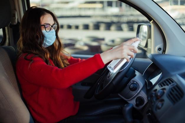 Молодая девушка в маске коронавируса, сидя в машине, держа спрей
