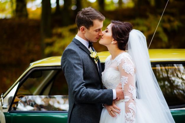 新婚夫婦がキスし、屋外の散歩での結婚式の日に笑顔します。花の花束と面白い花嫁。