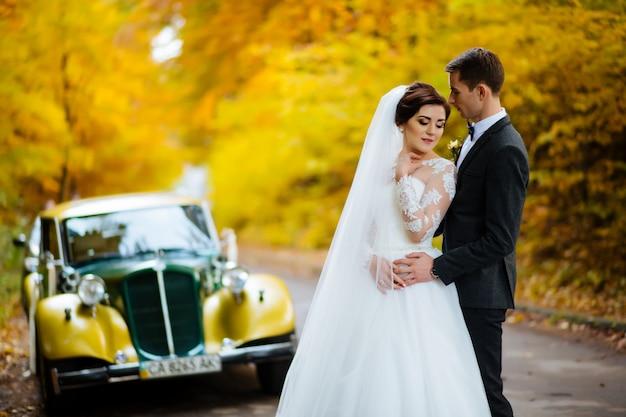結婚式のカップルの背景の結婚式の車