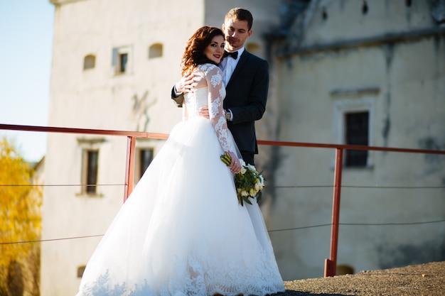 幸せな笑顔の新婚夫婦の野外を歩いている、キスをし、結婚式の日に抱きしめる