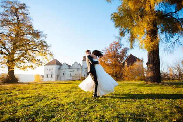 彼の腕の中でブルネットの少女とハンサムな若い男。ロマンチックな新婚夫婦が公園で踊ります。