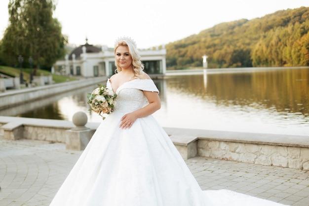 Девушка с белыми волосами говорит о природе, в лесу, на озере. свадебное платье.