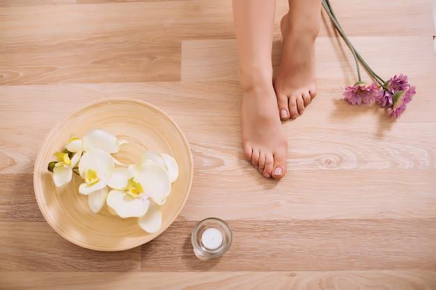 木製の背景に花模様の女性の足