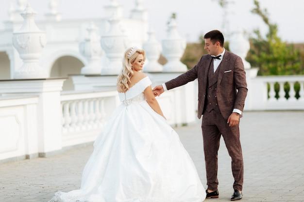 Жених и невеста в день свадьбы, прогулки на свежем воздухе на весенней природе. молодоженов, счастливая женщина молодоженов и мужчина, охватывающей в зеленом парке. любить свадьбы пара на открытом воздухе.