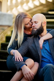 Молодая пара закрыла глаза, стильно оделась, сидя на ступеньках, напротив исторического здания