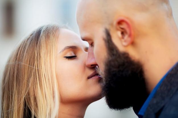 路上でキス美しいカップルの若いアウトドアファッションの肖像画