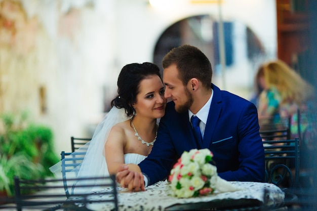 幸せな新婚夫婦がカフェのテーブルでキス