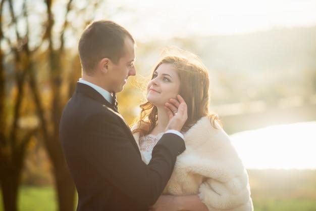 少女とウェディングドレスを探しているカップルの肖像画、彼女の頭に花の花輪を飛んでいるピンクのドレス、彼らは抱擁し、ポーズ