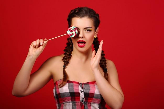 閉じる。カラフルなロリポップを保持している赤い唇とブルネットの少女。赤い壁に美容モデルポートレート甘いお菓子。