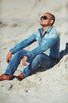 Парень сидит на песке, загорелая джинсовая одежда