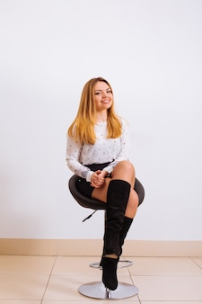 Портрет ошеломляющей модной модели, сидящей в кресле в стиле модерн. бизнес, элегантная деловая женщина.
