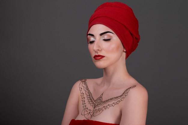 Модный портрет красивой чувственной женщины, закрытого очима, красной шали, вечернего макияжа и татуировки хной на коже