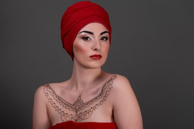 Ближневосточная красавица в платке с красными губами изолировала серую стену