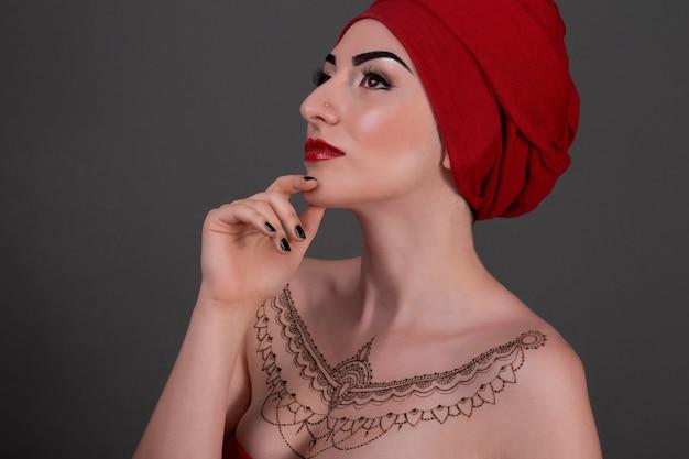 Молодой азиатский портрет женщины нося красный головной шарф изолированный на сером цвете.
