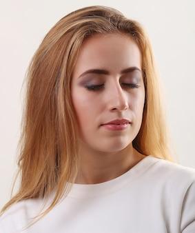 目で美しい女性のグラマーの肖像画は、新鮮な毎日のメイクとロマンチックなウェーブのかかった髪型のモデルを閉じました。皮膚のファッション光沢のある蛍光ペン、セクシーな光沢のある唇のメイクアップ、濃い眉