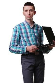 Человек с микрофоном держит ноутбук на белой стене
