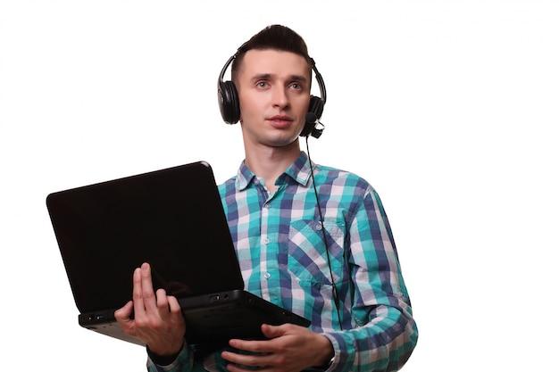 Молодой человек с гарнитурой держит ноутбук - человек в колл-центре с гарнитурой и ноутбуком на белой стене
