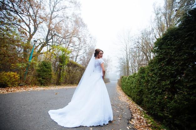 Красивая невеста в свадебном платье и свадебный букет, счастливая женщина молодоженов со свадебными цветами, женщина со свадебным макияжем и прической. великолепная молодая невеста на открытом воздухе. невеста ждет жениха. невеста