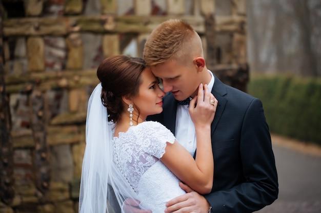 庭で手を繋いでいる白い服でロマンチックなおとぎ話夫婦