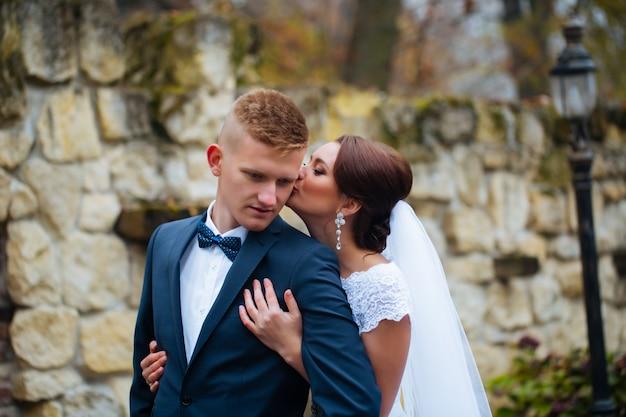 Свадебные красивые молодые пары стоят на улице