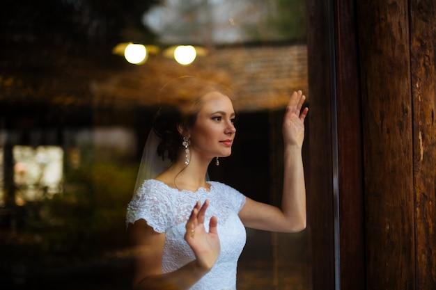 Невеста в платье над окном. солнечный день. солнечный свет