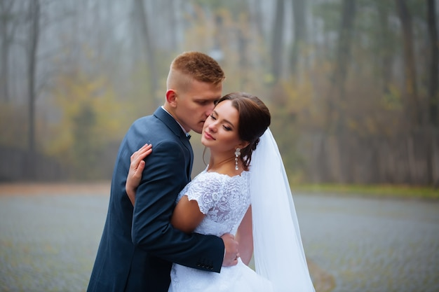 Свадебный жених и невеста целуют влюбленную пару с букетом роз в зимний свадебный день наслаждайтесь моментом счастья и веселья. игривая новобрачная семья женщина и мужчина в любви. великолепная невеста