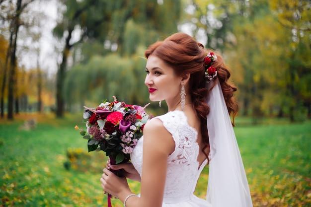晴れた日に公園で花束を持つ花嫁の肖像画