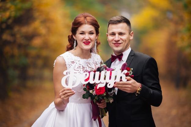 ウクライナのレタリングが付いている公園の新郎新婦