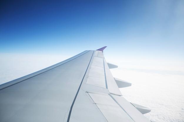 空の雲の上を飛んでいる飛行機の翼