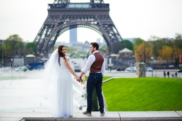 フランスのパリでちょうど結婚したカップル。エッフェル塔の近くの美しい若い新郎新婦。パリのコンセプトでロマンチックな結婚式
