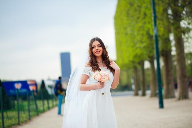 若い女性は白いレースのドレス、かかとの高い靴、パリを歩く