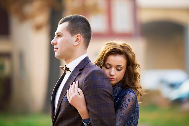 Красивая невеста, обнимая жениха со спины в парке