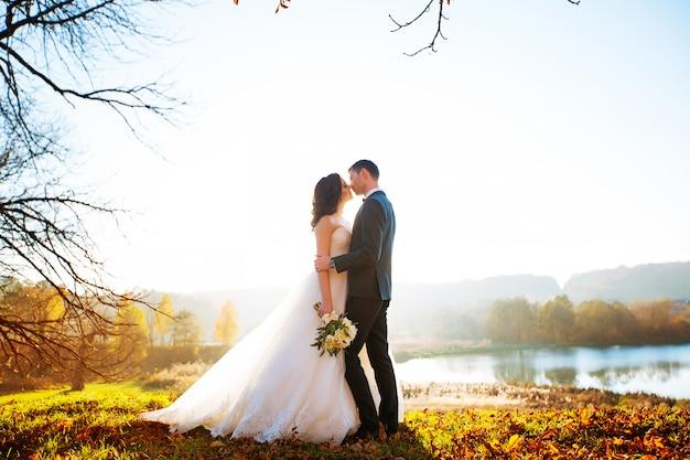 幸せな笑顔の新婚夫婦の屋外ウォーキング、キス、結婚式の日の採用