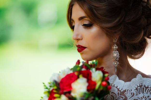 Брюнетка невеста в платье со свадебным букетом в парке на фоне зелени