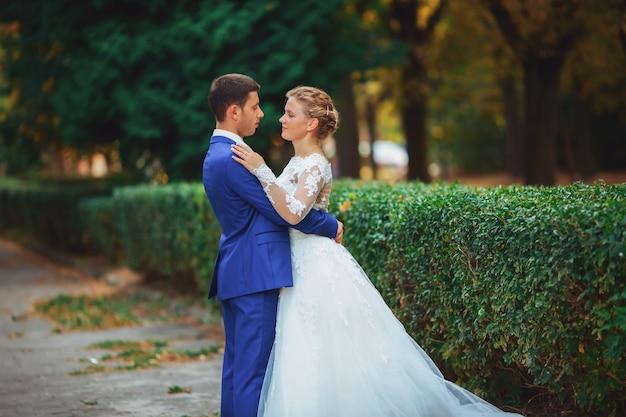Свадебная пара невесты в белом свадебном платье и жених гуляет в лесу