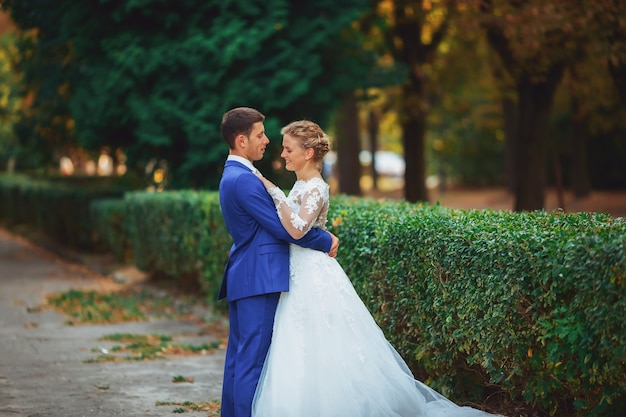Элегантная невеста и жених вместе позирует на улице в день свадьбы