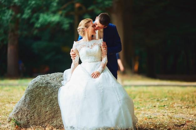 Красивая невеста в дорогом платье гуляя в лесах в природе держа руки