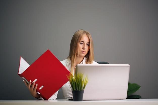 Элегантная коммерсантка сидя на ее офисе