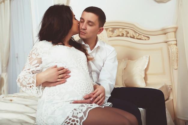 Портрет кавказской беременной женщины и ее мужа на диване у себя дома