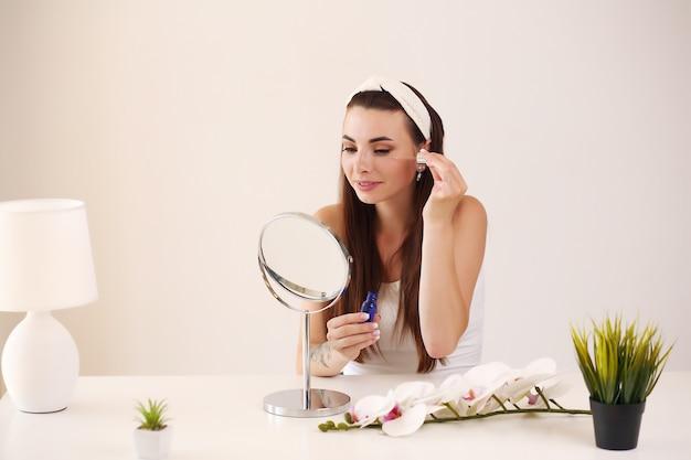 Молодая брюнетка женщина делает ее уход за кожей в зеркале