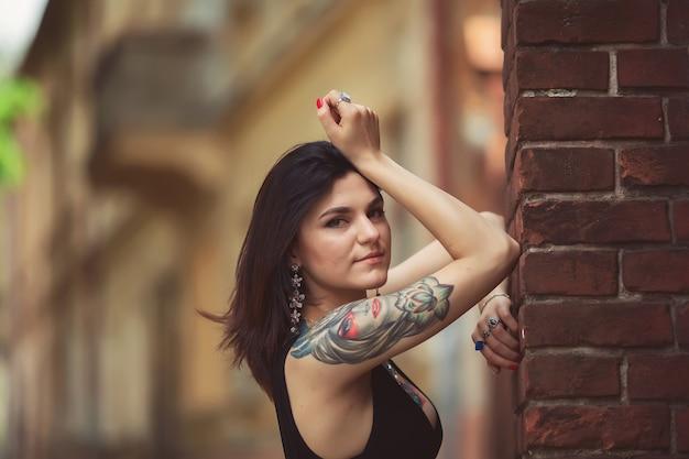 Красивая девушка в черном платье стоит возле архитектурных сооружений, позирует