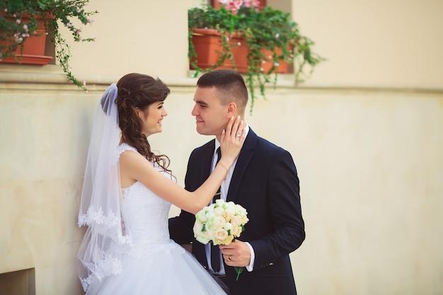 Свадебная фотосъемка. невеста и жених гуляя в город. супружеская пара обнимает и глядя друг на друга. держа букет. открытый, полное тело