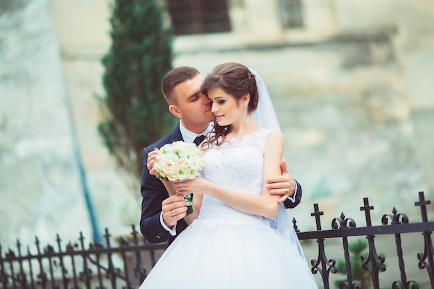 Свадебная пара красивая невеста и жених. молодожены. закройте счастливая невеста и жених на свадьбе обниматься. жених и невеста в парке. свадебное платье. свадебный букет цветов