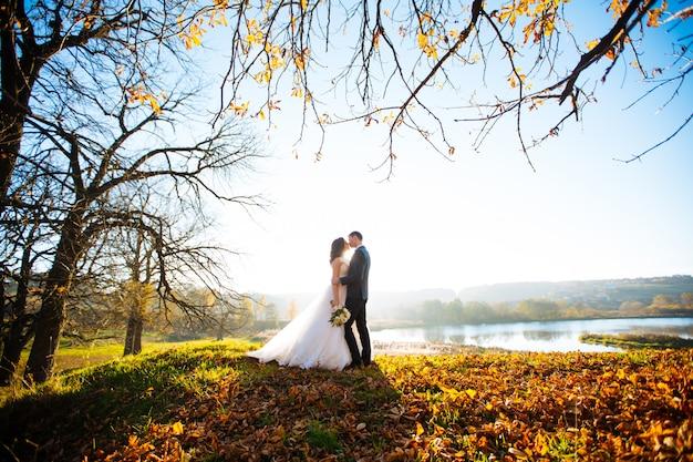 新婚夫婦は、屋外の散歩で結婚式の日にキスと笑顔します。花の花束と面白い花嫁。