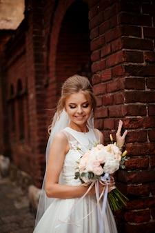 Красивая невеста с букетом цветов свадьбы, привлекательная женщина в свадебном платье. счастливая новобрачная женщина. невеста с свадебный макияж и прическа. улыбающаяся невеста. день свадьбы. шикарная невеста брак.