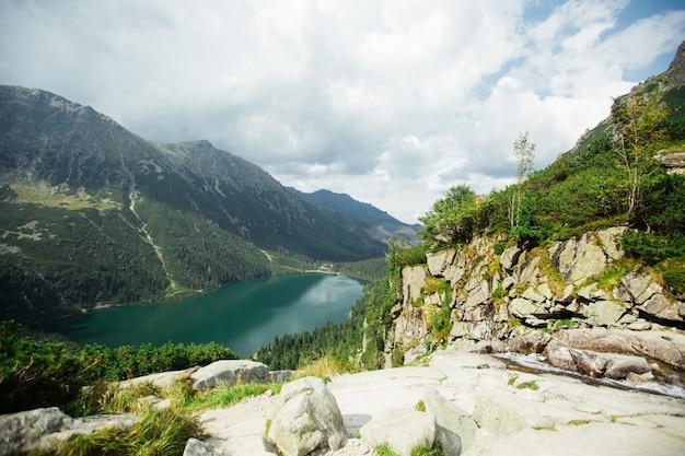 Татранский национальный парк, польша. панорама знаменитые горные озера морской глаз или озеро морской глаз в летнее утро долина пяти озер.