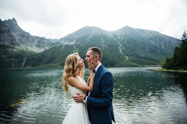 美しい白いドレスと美しい緑の山々と青い水と湖を見下ろす花嫁と花嫁