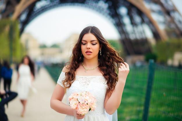 Милая невеста в вуали позирует на открытом воздухе