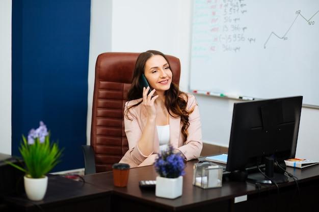 Молодая женщина в офисе решает бизнес по телефону